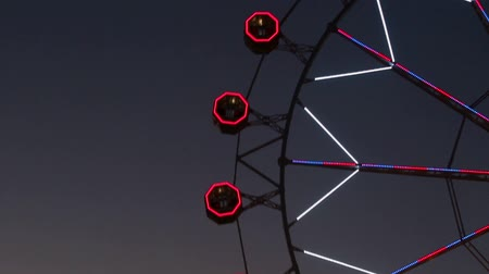 tontura : Close-up of Ferris wheel by rotating at night with large colorful of led lights and motion.Normal speed.