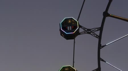 heyecan verici : Close-up of Ferris wheel by rotating at sunset with large colorful of led lights and motion.Slow speed.