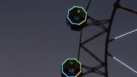 szédülés : Close-up of Ferris wheel by rotating at sunset with large colorful of led lights and motion.Normal speed.