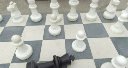 porażka : Giant chessboard on the street with the black king fallen and surrounded by white pawns. Concept of victory and defeat.Camera movement: Tilt down.