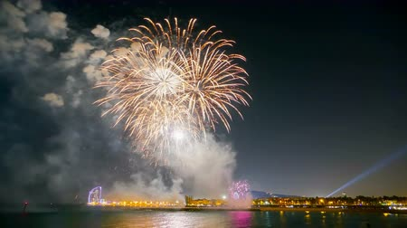 water display : Many explosions with colorful fireworks over the sea with reflection in water, in Barcelona.Time Lapse.