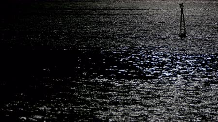 holdfény : Reflection of moonlight with a light buoy and a boat passing on the top right of the scene. Stock mozgókép