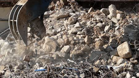 smashing : Close-up of heavy demolition machinery at work, crumbling and moving rubble concrete. Slow Motion Stock Footage