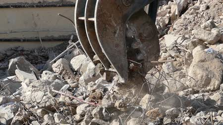reinforced concrete : Close-up of heavy demolition machinery at work, crumbling and moving rubble concrete. Slow Motion Stock Footage