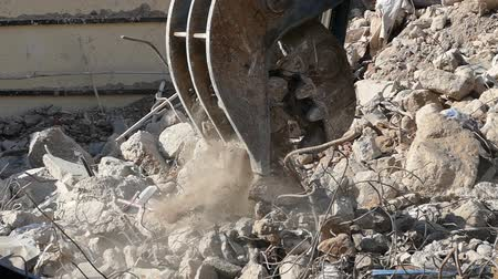 deconstruction : Close-up of heavy demolition machinery at work, crumbling and moving rubble concrete. Slow Motion Stock Footage
