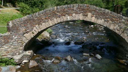 abundante : Front view of a small stone bridge of Romanic style, in a mountain river on the Pyrenees of Andorra.