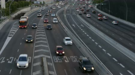 two rows : Blurred evening urban traffic scene with a top and rear view access roads to Barcelona.With cars stopped and then set in motion.Time Lapse. Stock Footage