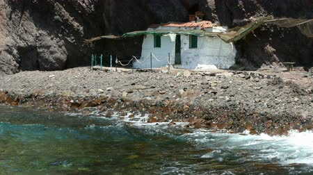 kanarya adaları : Little and isolated hovel. Small lonely house excavated into the rock of a cliff on the coast. Stok Video