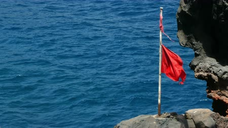 advertir : Seascape with broken red flag moving by the wind, with a background of ocean and cliffs, transmitting feeling of danger.