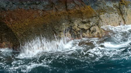 sheen : Close up of the surface of the cliff, with the movement of the waves. Stock Footage