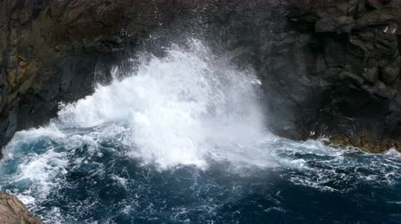 comes : Big waves crashing on a cliff of lava rocks on the coast of the island of La Palma, Canary Islands, Spain.
