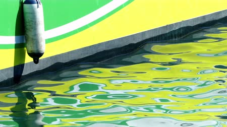 hajótest : Detail of the hull of a boat with bright reflections moving on the surface of the sea.