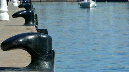 moorage : Closeup of old bollard on the seaport of Barcelona, with a little pleasure boat sailing in the background.Time lapse. Stock Footage