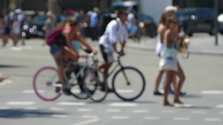 telephoto lens : Side view blurred pedestrians crossing the street in the city of Barcelona in summer.Slow Motion