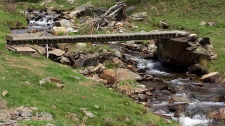 telephoto lens : Old wooden footbridge over a river in the Pyrenees of Catalonia Stock Footage
