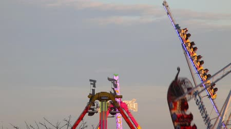 frisson : Fairground attractions by rotating at sunset with large colorful neon lights and motion.Time Lapse