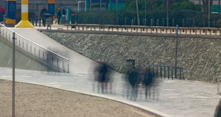 bread pan : People walking along the beach in Barcelona on a winter day.Time Lapse 4K - Wake effect.Smooth motion camera: Pan.