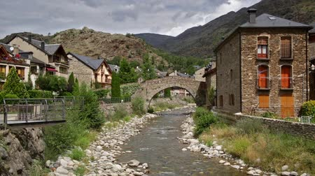 pyreneje : Esterri dAneu, Pyrenees village of Catalonia, with moving clouds and sunlight, view of the river with an old stone bridge. Time Lapse