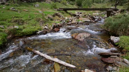 natural resource : Mountain river with old wooden footbridge in the Pyrenees of Catalonia (Spain) .Time Lapse