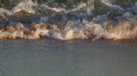 Close-up of the seashore where the waves break, with the evening light.Front view Стоковые видеозаписи