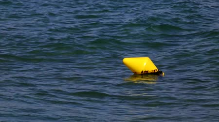 boa : Old yellow buoy floating in the sea with the smooth movement of the waves.
