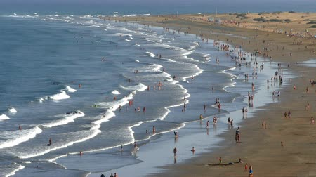 kanarya : Aerial view of the English Beach, Canary Islands. Panoramic with many people walking with their own reflection in the water, and the movement of waves at sunset, in the zone of Maspalomas, island of Gran Canaria, Spain. Stok Video