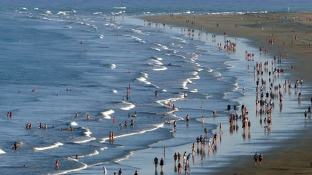 kanári : Aerial view of the English Beach, Canary Islands.Time lapse. Panoramic with many people walking with their own reflection in the water, and the movement of waves at sunset, in the zone of Maspalomas, island of Gran Canaria, Spain. Stock mozgókép