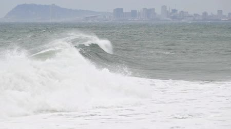 Surge with big waves, strong wind and poor visibility. Two play speeds: Real time and Slow motion. Groundswell in the Mediterranean sea with Barcelona city in the Background.