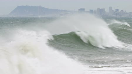 Surge with big waves, strong wind and poor visibility. Groundswell in the Mediterranean sea with Barcelona city in the Background.Time Lapse.