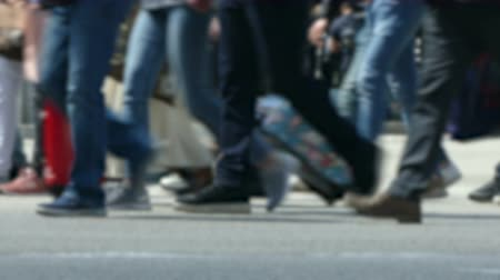 Side view blurry pedestrians walking. Detail of legs crossing a street in the city of Barcelona with traffic of background.