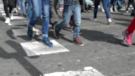 Front view blurry pedestrians walking.Slow motion. Detail of legs crossing a street in the city of Barcelona.