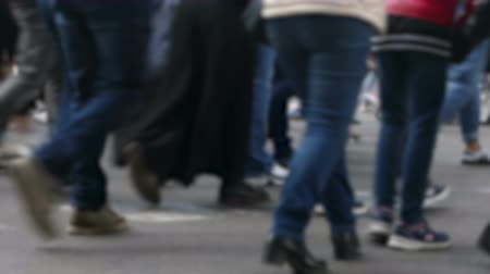 Side view blurry pedestrians walking. Detail of legs crossing a street in the city of Barcelona.