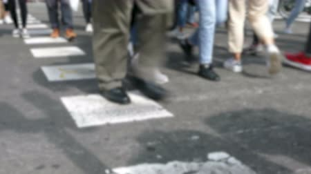 Front view blurry pedestrians walking. Detail of legs crossing a street in the city of Barcelona. Стоковые видеозаписи