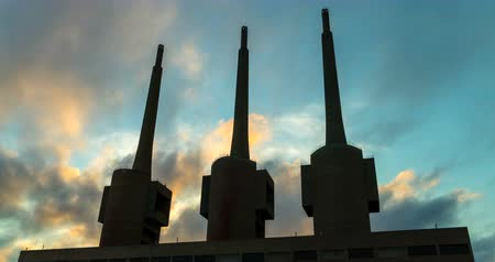 Ancient thermal power station in Sant Adria, province of Barcelona.Hyper Lapse. Silhouette of three chimneys with clouds in motion on sunset sky background. Smooth camera movement: Zoom in. Стоковые видеозаписи