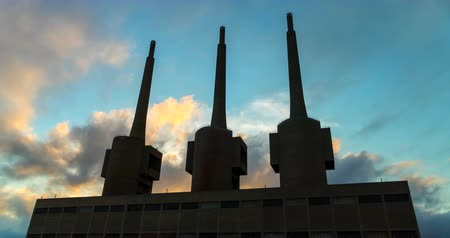 дымоход : Ancient thermal power station in Sant Adria, province of Barcelona.Time Lapse. Silhouette of three chimneys with clouds in motion on sunset sky background.