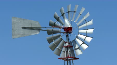 Old vintage style windmill rotating on a sunny day with blue sky background. Symbol of the development of renewable energies.