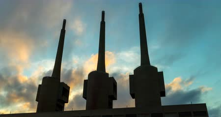 Ancient thermal power station in Sant Adria, province of Barcelona.Hyper Lapse. Silhouette of three chimneys with clouds in motion on sunset sky background. Smooth camera movement: Panning right.