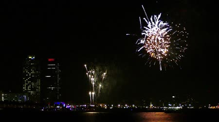 Many explosions with colorful fireworks over the sea with reflection in water, in Barcelona.Slow Motion