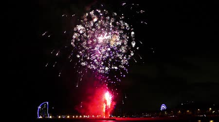 Many explosions with colorful fireworks over the sea in Barcelona.Slow motion