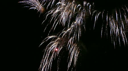Close up of many explosions and golden wakes of fireworks.