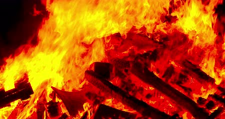Close-up of a bonfire with the flames in motion.Smooth camera movement: Panning Right. Стоковые видеозаписи