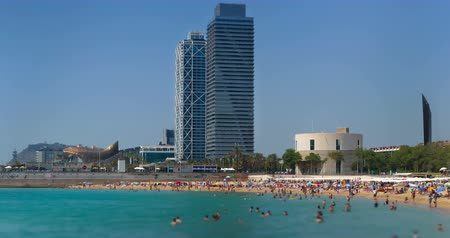 Beaches and architecture. Activity on the beaches of the city of Barcelona with people in the foreground blurred and skyscraper background, a sunny day. Time lapse. Smooth camera movement: zoom out.