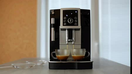 dois objetos : Coffee machine pours black coffee in two glass cups