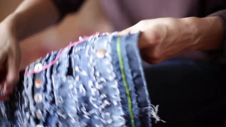 lem : The girl is sewing a bag. The hands are close-up. Dostupné videozáznamy