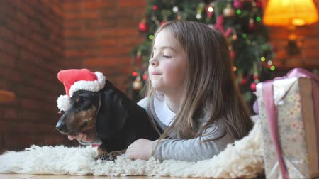 beautiful girl with sowai favorite girl in santa claus cap playing lying on white carpet near festive Christmas tree