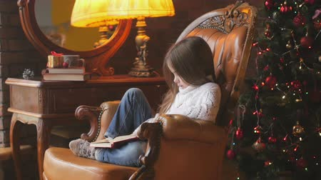 beautiful little girl is reading a book while sitting in a chair near a festive Christmas tree