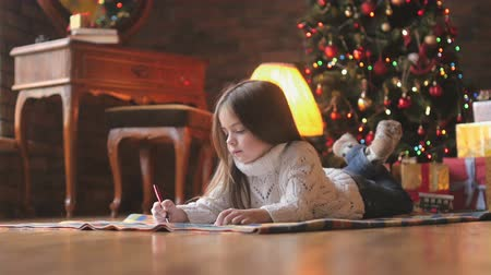 beautiful little girl in a white knitted sweater lies on the floor and writes a letter to Santa Claus, in the background a festive Christmas tree and a lot of presents