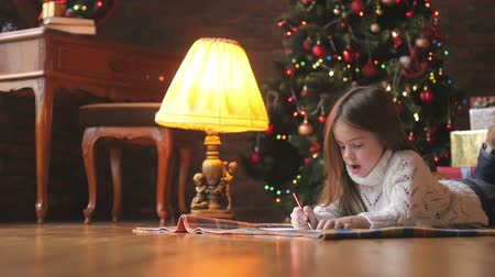 a beautiful little girl in a white knitted sweater lies on the floor, composes and writes a letter to Santa Claus, in the background a festive Christmas tree and a host of gifts