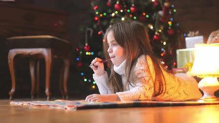 expectativa : a beautiful little girl in a white knitted sweater lies on the floor, composes and writes a letter to Santa Claus, in the background a festive Christmas tree and a host of gifts
