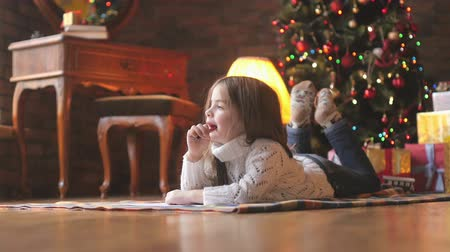 фон : beautiful little girl in a white knitted sweater lies on the floor and writes a letter to Santa Claus, in the background a festive Christmas tree and a lot of presents